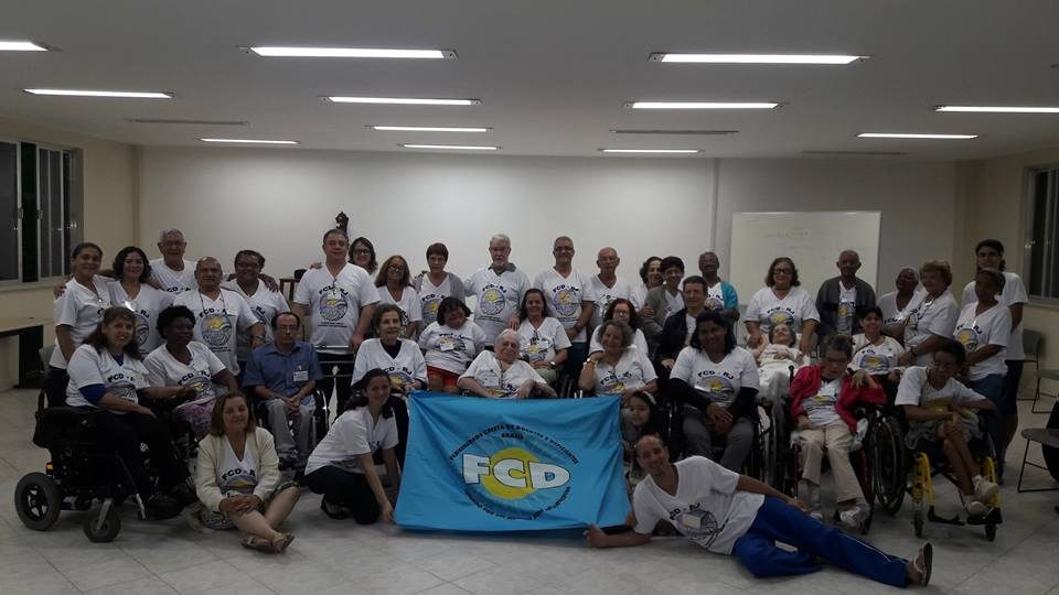 Membros Fraternistas na Assembleia Estadual do RJ realizada na Casa de Retiros, Padre Anchieta em São Conrado, Rio de Janeiro. Foto com mais de 40 pessoas e a bandeira da FCD. A maioria é cadeirante.