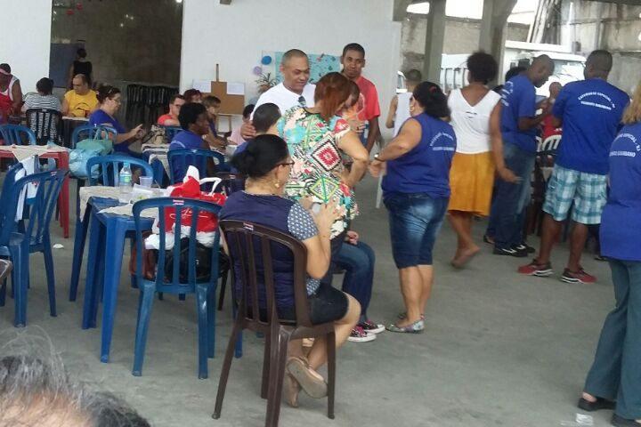 Muitas pessoas reunidas para celebrar a Festa da Primavera. São jovens e adultos com alguma deficiência Intelectual. Usam camiseta de cor azul e muita animação.