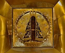 Nicho da Imagem de Nossa Senhora Aparecida que se encontra na Basílica Nacional em Aparecida (SP). Imagem de cor escura, com manto doutado dentro de um quadro de bronze c cores fortes da cor dourada.