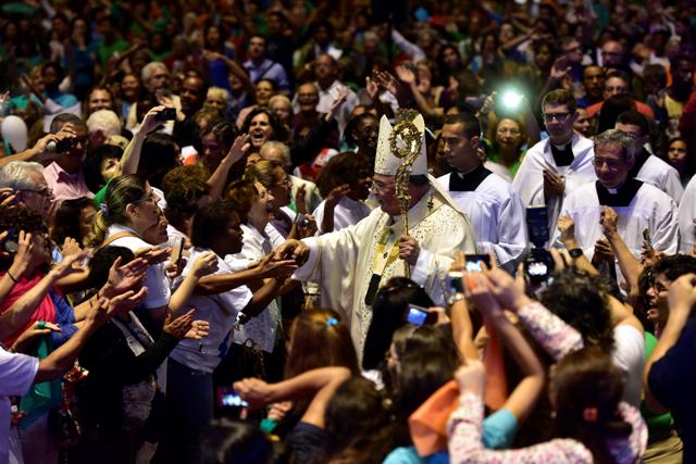 Dom Ornai usando mitra e cajado caminhando junto à uma multidão de fiéis na Catedral do Rio.