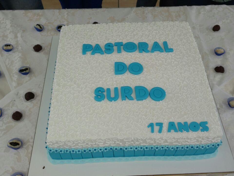Bolo de cor branca e com os seguintes dizeres: Pastoral dos surdo - 17 anos da Comunidade da Igreja da Penha.