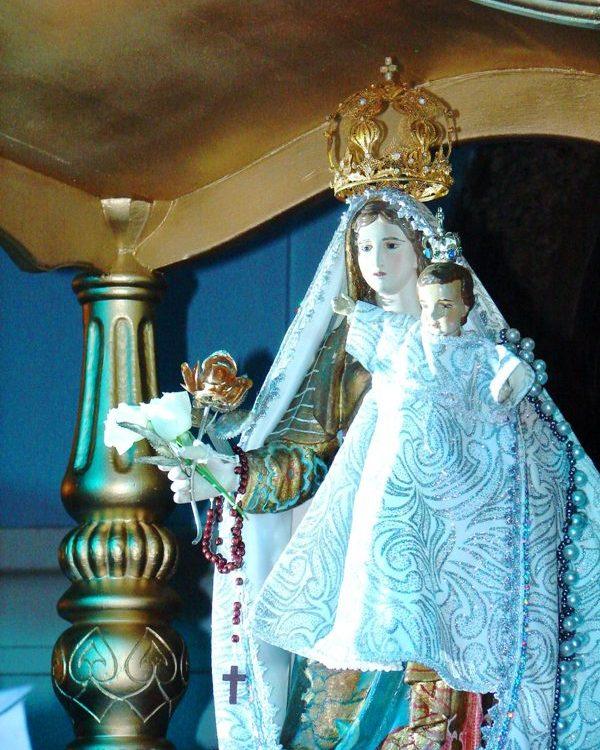 Imagem de Nossa Senhora da Penha, com um manto azul, o menino Jesus em seu colo. Ele usa um manto branco e azul.