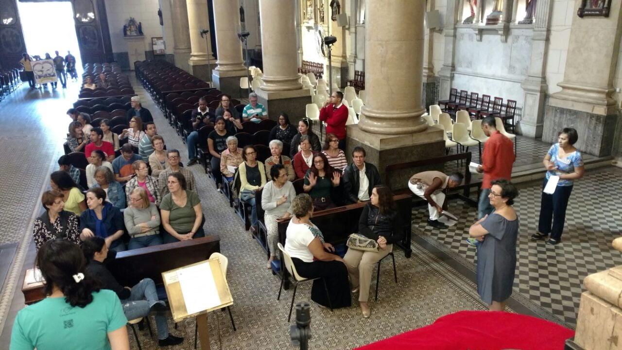 Sursos e cegos na Igreja, todos em pé participando da Adoração ao Cristo jesus, na Igreja Matriz da Praça Onze.