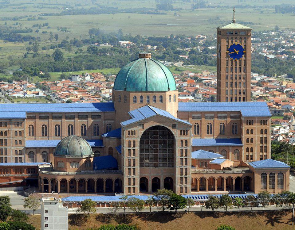 Templo da Basílica Nacional em Aparecida no Estado de SP. Edifício monumental feito em tijolos, sem pintura externa, uma torre com relógio e uma cúpula verde imensa.