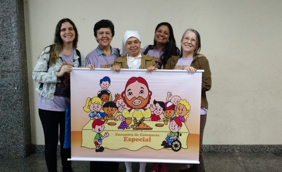 4 mulheres seguram o cartaz que mostra Jesus e as crianças. O curso foi dado em Niterói no dia 19 de agosto. membros da Pastoral do Surdo de Niterói participaram do evento. no dia 19 de agosto.