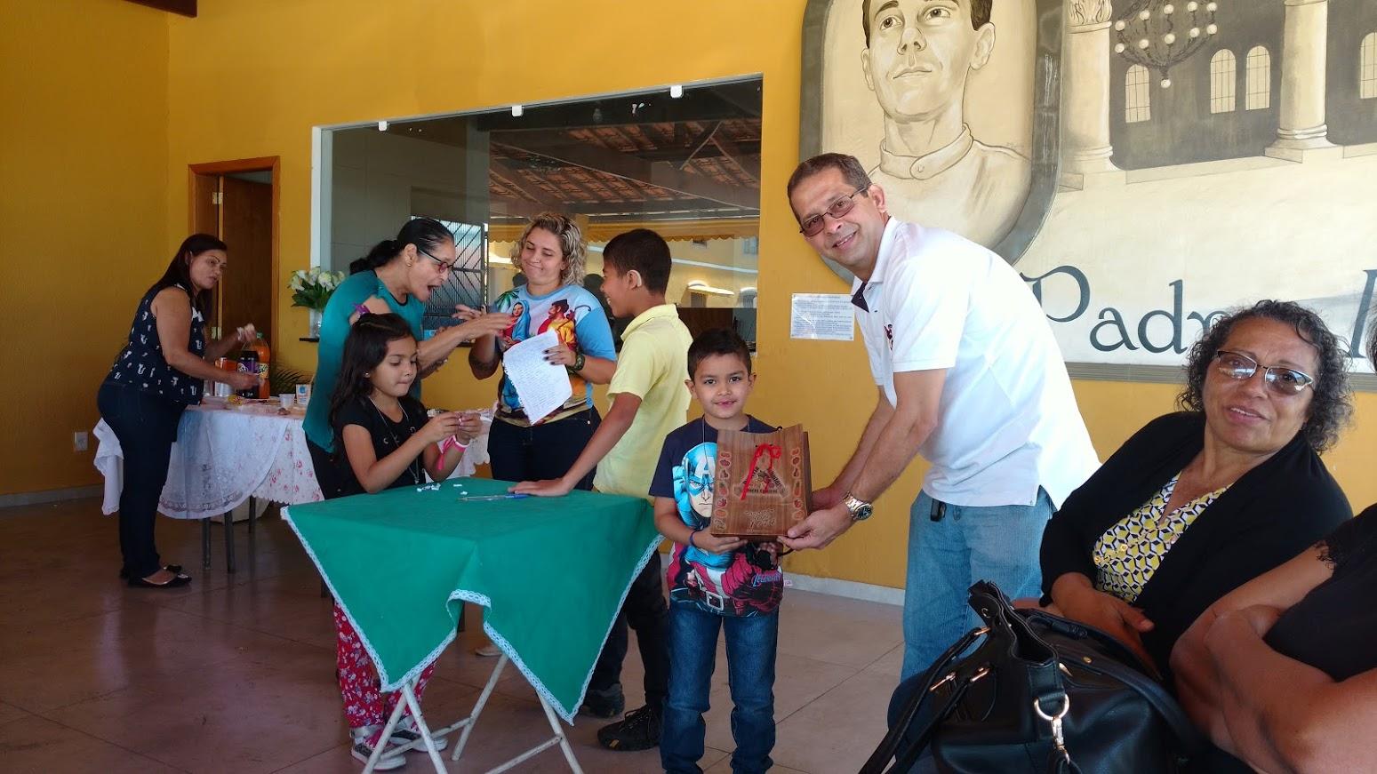 Surdo recebndo das mãos de uma criança um pacote de doces cristalizados. Salão de Convivência, Na Igreja de Campo Grande.