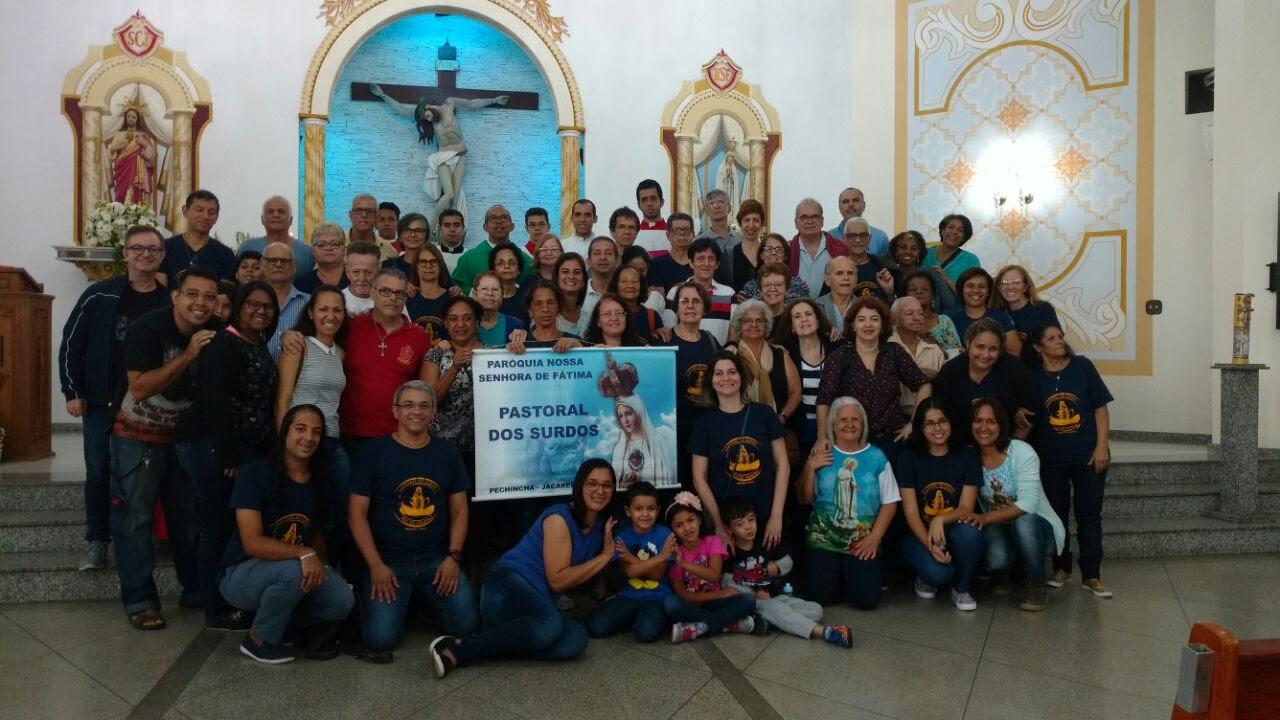 Grupo de surdos e ouvintes cerca de 50. todos em pé em frente ao altar com o padre Evandro na foto oficial em frente ao altar. Há um banner com o texto: Pastoral do Surdo, Jacarepaguá.
