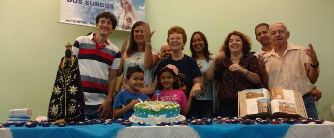 Grupo de surdos em volta da mesa com um bolo com o desenho de Nossa Senhora de Fátima. todos cantam os parabéns em LIBRAS.