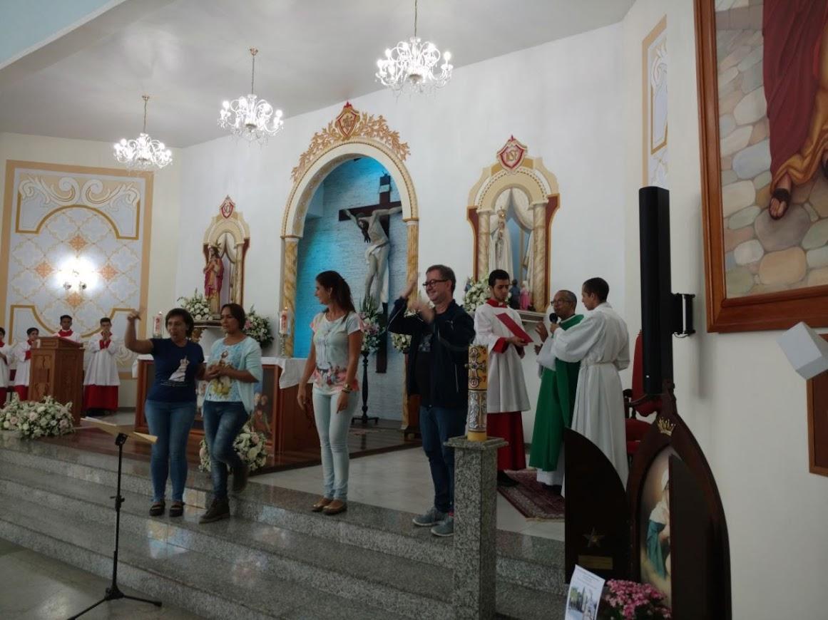 Altar de Nossa Senhora de Fátima, padre de roupa de cor verde, com os coroinhas ao seu lado. Diversos intérpretes fazem a tradução em LIBRAS.