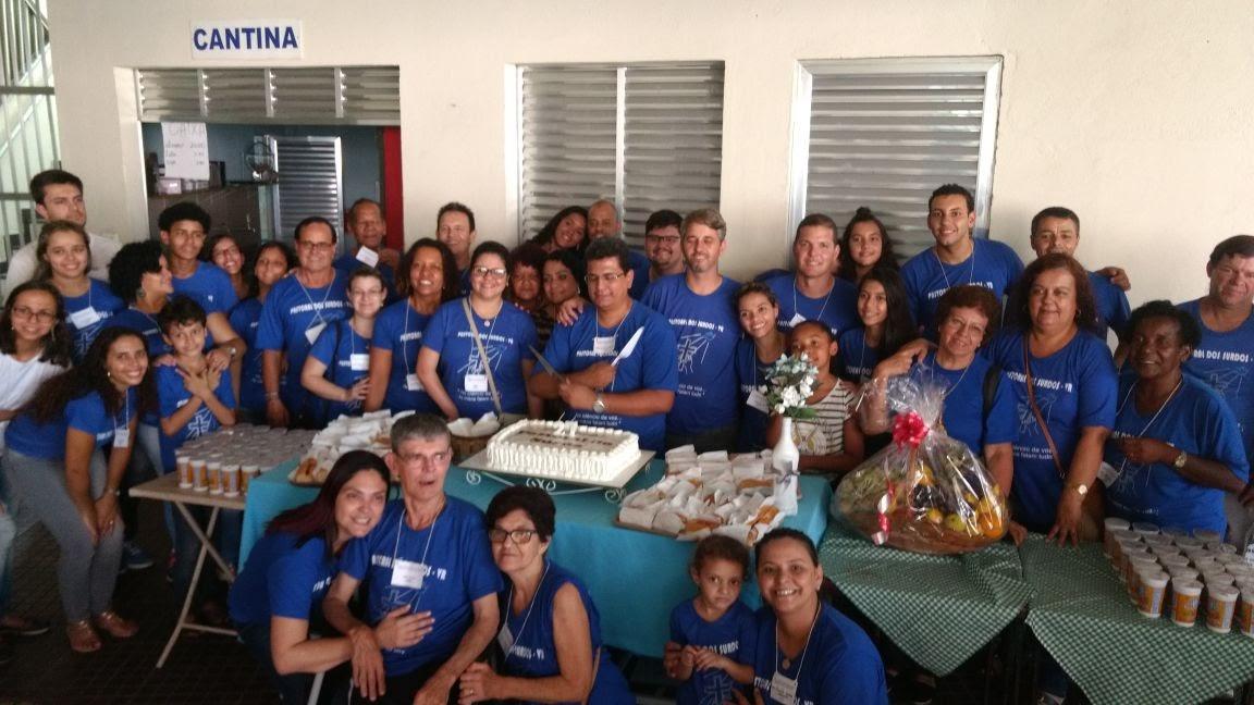Um bolo gigante, muita gente em volta, usando camisets de cor azul, cantando os parabéns.