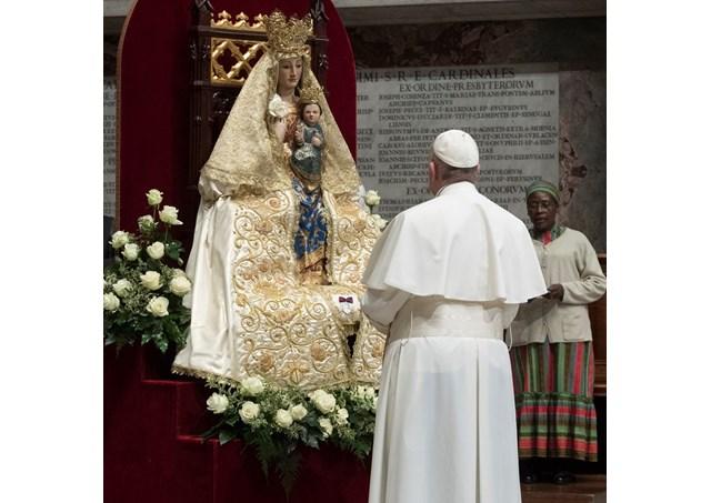 Linda imagem de Maria, de manto branco com flores brancas em volta da image, Papa Francisco de pé reza em silêncio.