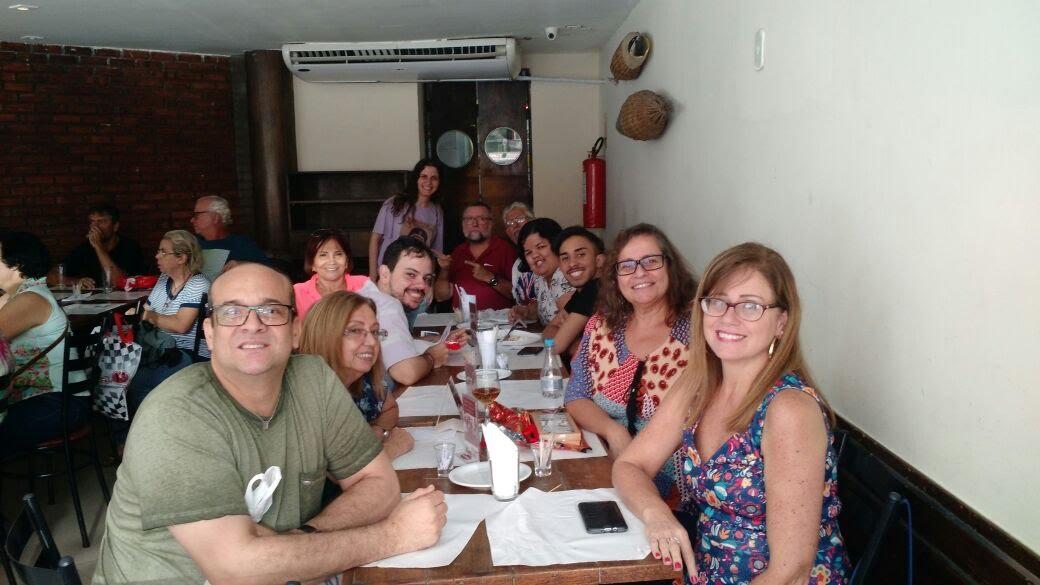 Surdos sentados à mesa almoçando num restaurante de Niterói.