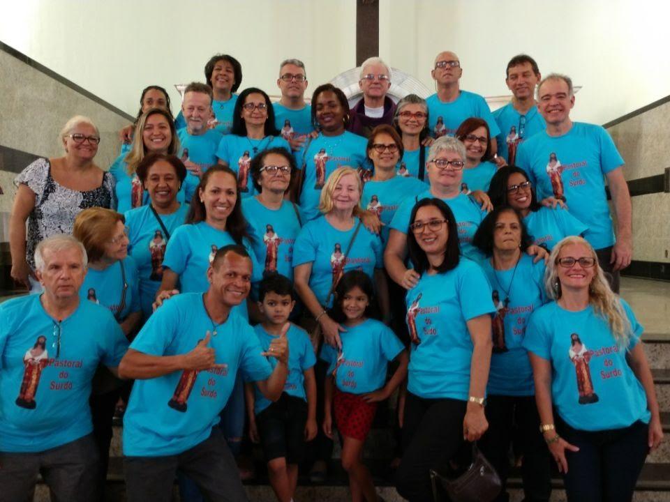 Grupo de 26 surdos e intérpretes em frente ao altar mor. todos co camiseta azul em pé para a foto oficial. Missa de 18 anos de fundação. Bairro da Penha.