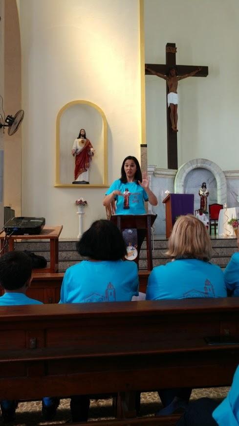Uma intérprete em pé faz a interpretação da Missa em LIBRAS. Igreja bom Jesus da Penha