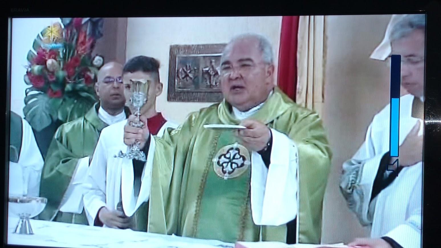 Dom Orani na Missa no momento do Encerramento da Oração Eucarística. Usa paramentos verde. Com a patena elevada em sua mão e o diácono ao seu lado, com o cálice elevado.