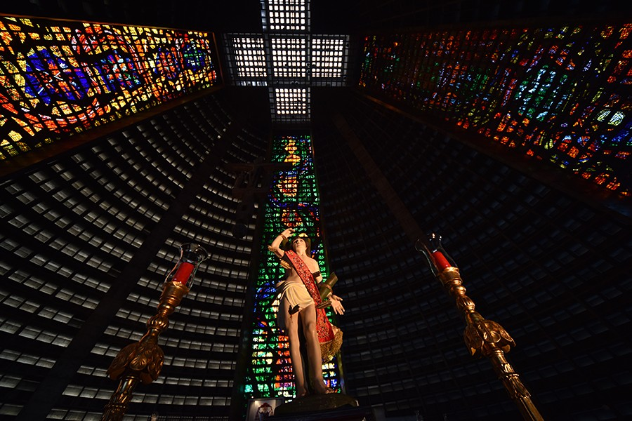 Imagem de São Sebastião com duas vela de cada lado. Estaa a imagem bvem no centro da Catedral do Rio. Em cim, no teto, forma -se uma cruz com a arquitetura da mesma.