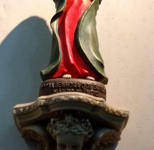 Imagem de Nossa Senhora dos Surdos, Mãe do Silêncio no altar lateral da Basílica do Imaculado Coração de Maria no Méier. Ela tem o tamanho de 30 cm, vestido de cor vermelha e manto verde. Tem as mãos cruzadas no peito, tem um olhar terno e sereno.