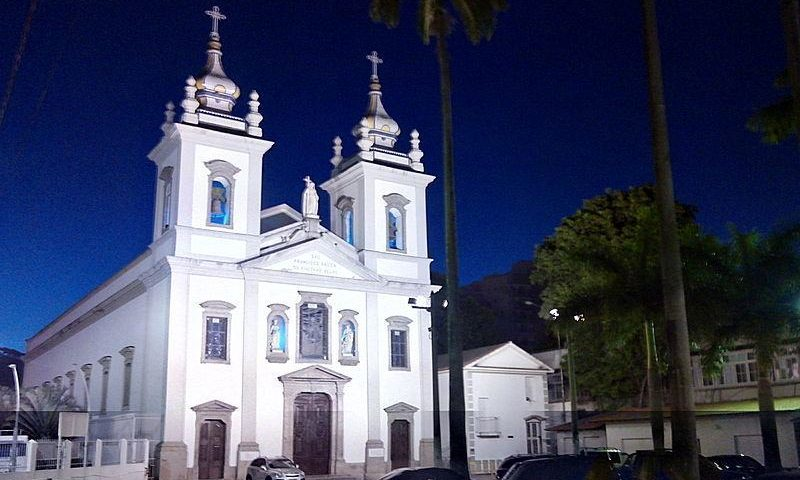 Foto da Igreja de São Francisco Xavier - Tijuca - duas grandes torres, de cor branca e nave central bem longa. Em frente com coqueiros e estacionamento em frente da Igreja e com alguns carros.