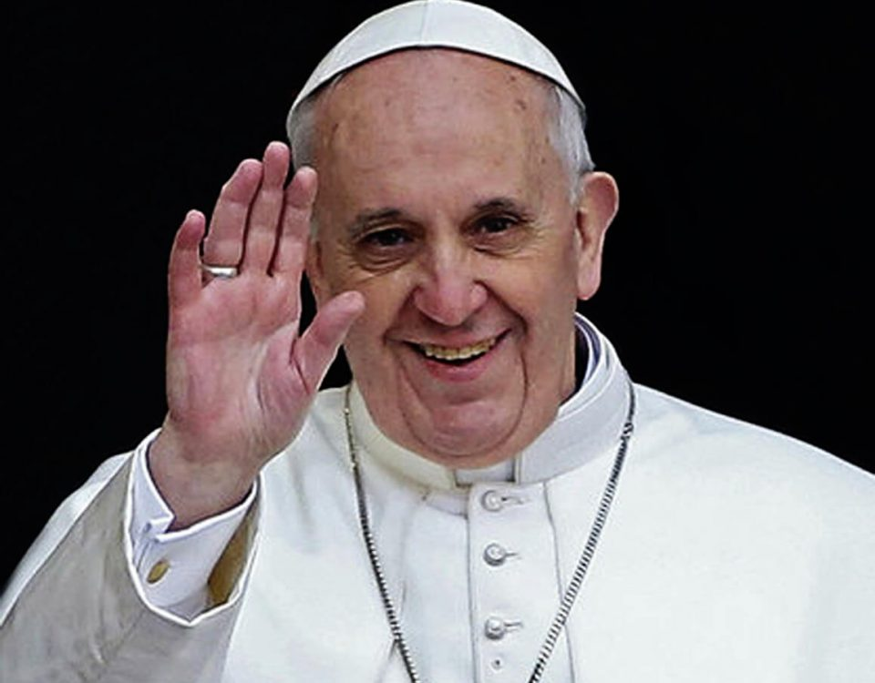Foto do Papa Francisco acenando com as mãos e um bonito sorriso. Usa batina branca, solideu na cabeça e anel .