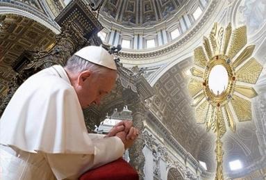 Papa Francisco de joelhos diante do ostensório. Um objeto de metal, em forma de sol com raios. Dentro há um Círculo em que se coloca a hóstia consagrada.